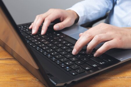 Businesswomans hands typing on laptop keybord.