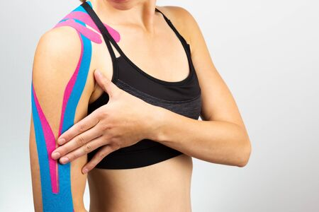 Kinesiotaping, kinesiology. Female athlete with kinesiotape, muscle tape on shoulder Фото со стока