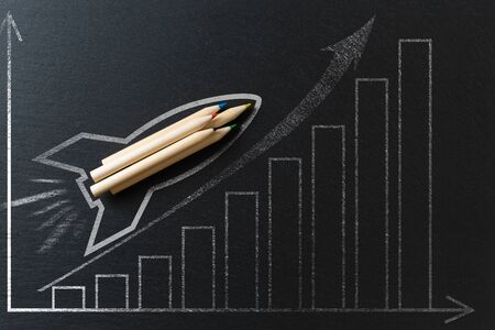 Drawing of a rocket on a black metal background with pencils. Startup concept Zdjęcie Seryjne