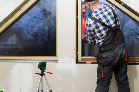 Handyman, construction man installing PVC window in a new insulated and filled dry wall attic. Stock Photo