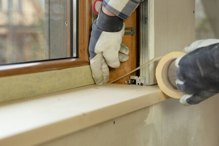 home improvement handyman installing window in new build attic by using leveler and laser leveler