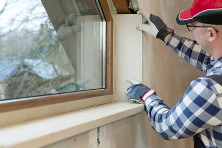 home improvement handyman installing window in new build attic by using leveler and laser leveler Stock fotó - 138222708