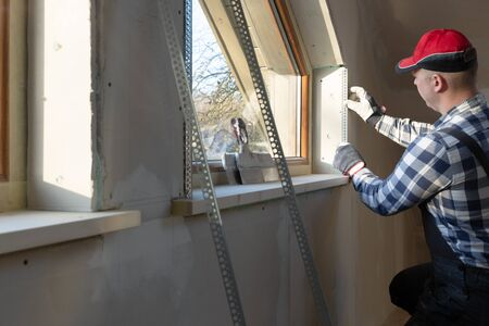 home improvement handyman installing window in new build attic by using leveler and laser leveler Stock fotó - 138202030