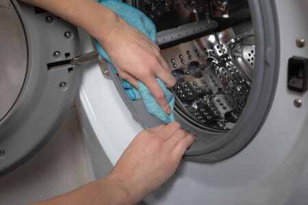 Cleaning and loading white washing machine