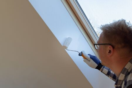Home improvement concept, handyman painting a wall with a white paint near roof window in attic