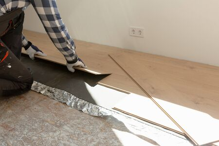 Construction worker installing laminate floor in a new renovated attic. Home improvement concept.