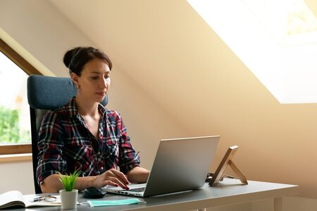 Young women working from home. Sitting in attic with laptop near roof window. New normal concept Archivio Fotografico