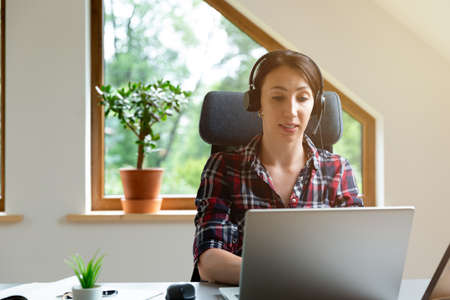 Bautifull women on a conforence call in home office. Working from home. Archivio Fotografico