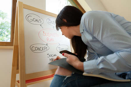 Business women preparing for meeting/e-learning at home by drawing on a child's whiteboard. Working from home concept.