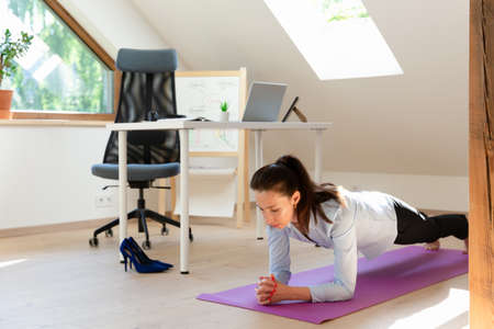 Beautiful women performing exercises and stretching in front of a laptop. Working at home, health concept.
