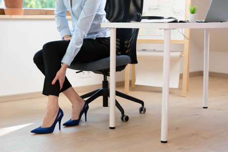 Woman massaging her legs after wearing high heels all day at work in office