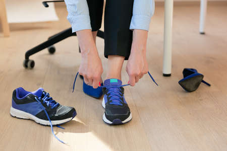 Woman changing high heels, office shoes after working day while sitting on the chair, ready to take a walk or run