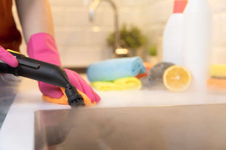 Women in rubber gloves cleaning black ceramic cooktop side with a hot steam cleaner and cleaning products blurred in background.