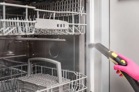 Women in rubber gloves cleaning dishwasher with a hot steam cleaner. Spring cleaning Banque d'images