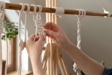 Woman relaxing and making macrame at home with different knots on a sunny day at home in attic. Stay at home hobbies.