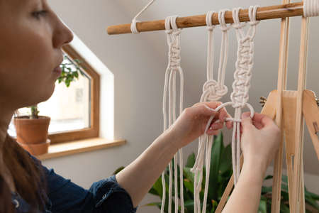 Women making macrame in a beautiful sunny day in attic. Stay at home hobbies. Banque d'images