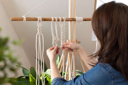 Woman relaxing and making macrame at home with different knots. Stay at home hobbies.