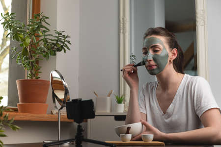 Beautiful woman making online course for facial beauty treatment at home.
