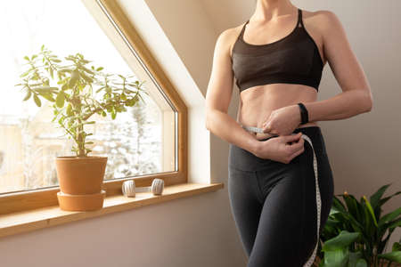 Young beautiful woman measuring waist with tape by a window in attic at sunny day. Healthy living and workout at home. Banque d'images