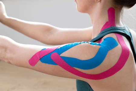 Closeup of a young fit womens shoulder with elastic therapeutic kinetic tape on her shoulder. Performing exercise at home. Kinesiology physical therapy.