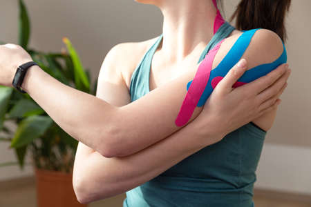 Young fit women wearing kinesio tape on her shoulder. Performing exercise at home. Kinesiology physical therapy.