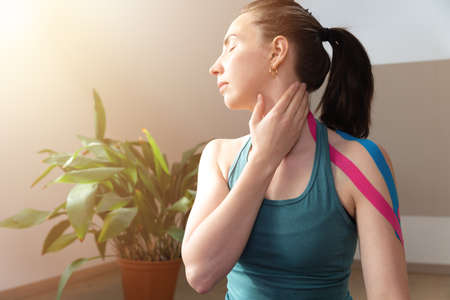 Young women touching her neck with hand and elastic kinesio tape on her shoulder. Performing exercise at home. Kinesiology physical therapy. Banque d'images