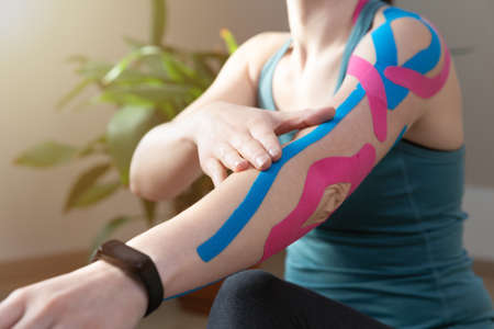 Young fit women showing on her elbow applied elastic kinetic tape. Kinesiology physical therapy.