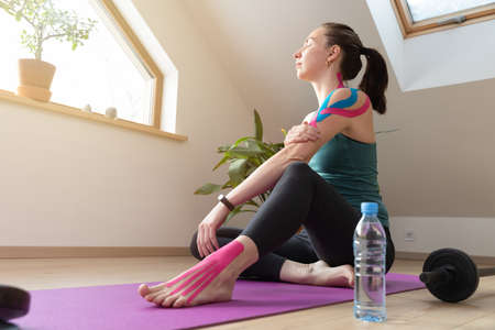 Young fit women relaxing while holding her hand. On shoulder elastic kinetic tape. Work out at home