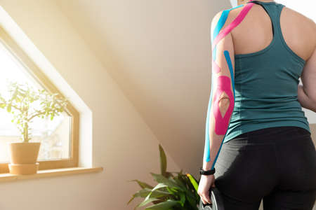 Young fit women standing by a window with sport weight in her hand. Applied elastic kinesiology tape on her arm. Muscle treatment, rehabilitation sport and physical therapy. Workout at home.