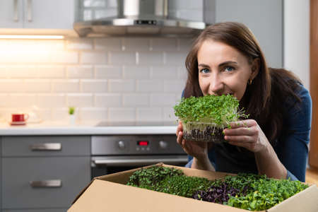Organic raw microgreens - women holding a countainer of microgreens in front of her face while smiling. Healthy eating superfood.