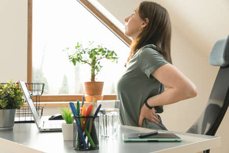 Working from home and exercise at home office. Beautiful woman stretching her back while sitting at workplace. Healthy living and body care. Stockfoto