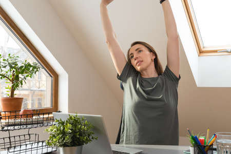 Woman stretching her hands up at office desk in a break from work at home office. Exercise and healthy living concept.