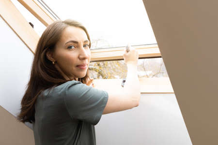 Women opening a window at home office and letting fresh air in. Healthy working environment in new normal business hours.