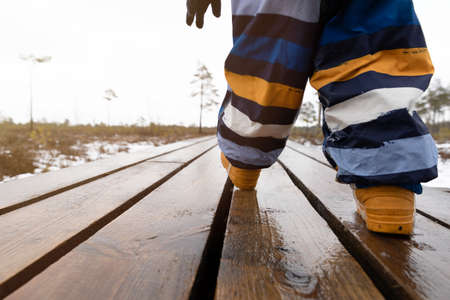 Boy child walking on a wooden pathway in a natural park. Close up of feet. Healthy active living concept. Stockfoto