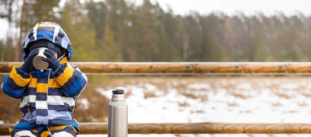 Young boy drinks hot beverage from a cup in a cold raini day. Resting, taking a break during hiking. Healthy living concept. Banner with copy space. Stockfoto