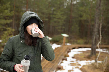 Women drinks beverage from cup and holds termos in other hand. Resting taking a break during hiking.