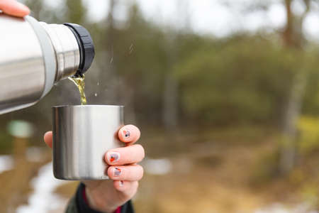 Youg beautifull women pouring beverage from termos to cup in a cold raini day. Healthy living and hiking. Stockfoto