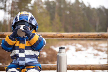 Young boy drinks hot beverage from a cup in a cold raini day. Resting, taking a break during hiking. Healthy living concept.
