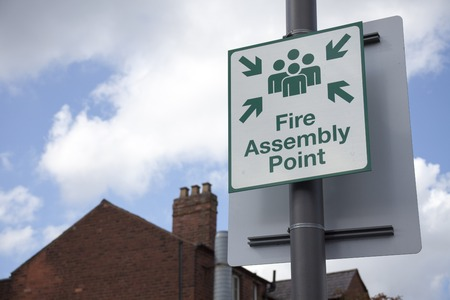 Sign fire assembly point on the street. Imagens