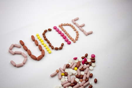 A suicide word, writing on the white background on pills with copy space.