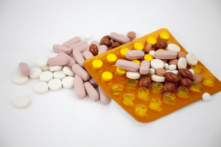 Colorful pills laying on the white background with copy space.