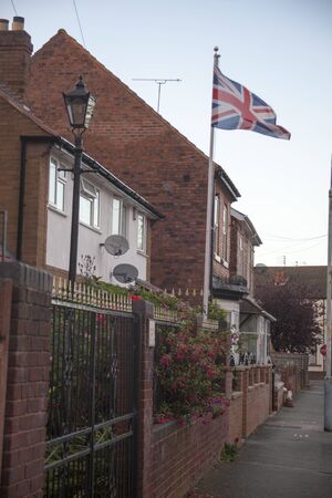 british culture: waving UK flag in the blue sky, Union Jack flag
