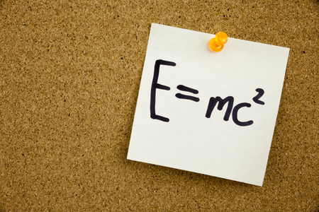 EQUATION E EQUAL MC2 in black ext on a sticky note pinned to a cork notice board