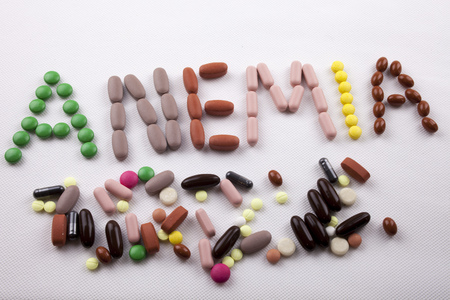 Hand writing Medical care concept written with pills drugs capsule word ANEMIA On white isolated background with space