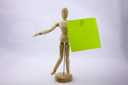 A green sticky note reminders on a white background holding by the wooden sculpture with text copy space