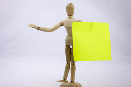 postit note: Two green sticky note reminders on a white background hoalding by the wooden sculpture with text copy space