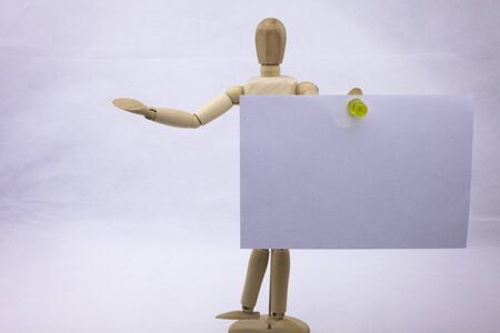 postit note: Two white sticky note reminders on a white background holding by the wooden sculpture with text copy space Stock Photo