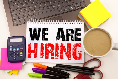 We Are Hiring Writing text in the office with surroundings such as laptop, marker, pen, stationery. Business concept for Recruitment and Job recruiting advertisement white background with space Banco de Imagens