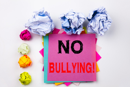 Writing text showing No Bullying written on sticky note in office with screw paper balls. Stock Photo