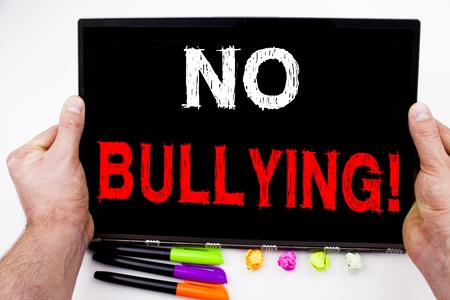 No Bullying written on tablet, computer in the office with marker, pen, stationery.